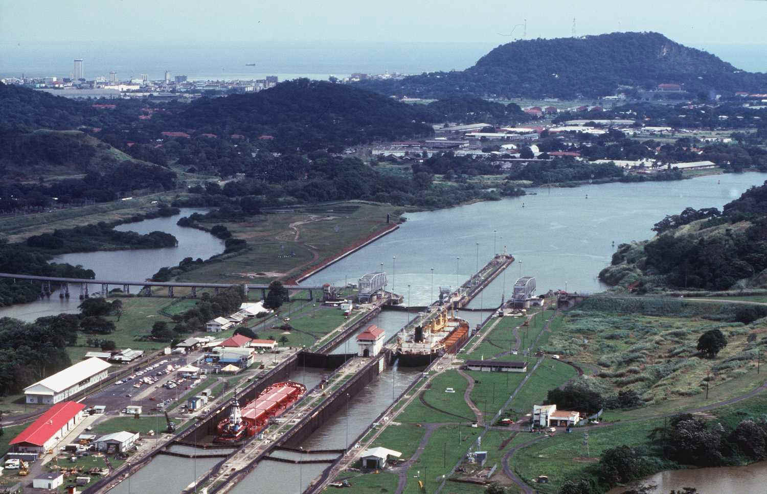 Panama Canal's Miraflores Locks (before 2000), the first set of locks for ships entering the Canal from the Pacific -- Albrook area and Ancon Hill in the right background; part of Panama City in distant left background  [Photo courtesy of Panama Canal Authority from its website, www.pancanal.com]